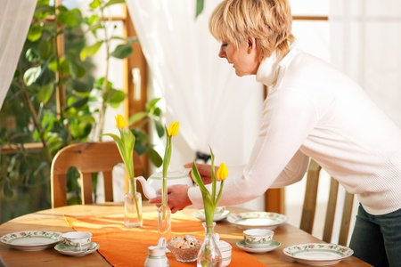 arranging: Woman setting the table for tea of coffee time in her domestic dining room, the table is decorated with tulip flowers, whole scene is sunlit