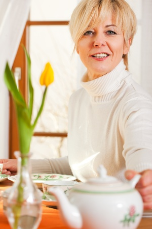 flatware: Woman sitting on a table for coffee or tea time grabbing for the coffee or tea pot, there are yellow tulip flower on the table, in the background is a window, whole scene is sunlit