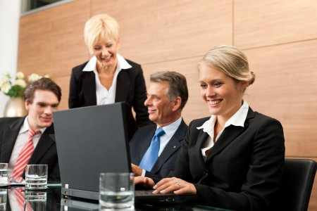 Business - team meeting in an office with laptop, the boss with his employees photo