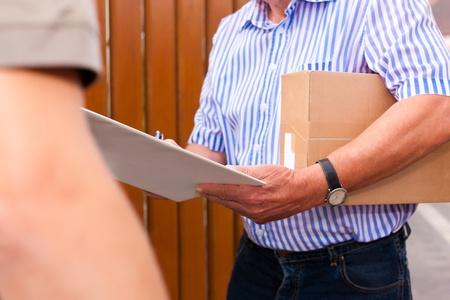 cartero: Servicio postal - la entrega de un paquete a trav�s de un servicio de entrega, el recibo del cliente la entrega Foto de archivo