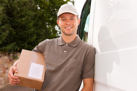 Postal service - delivery of a package through a delivery service; the postman is leaning on his van photo