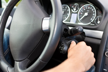 Man is starting his car; he is turning the ignition key under the wheel Stock Photo - 11530258