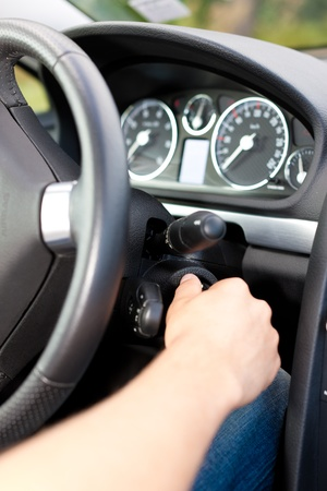 turn: Man is starting his car; he is turning the ignition key under the wheel