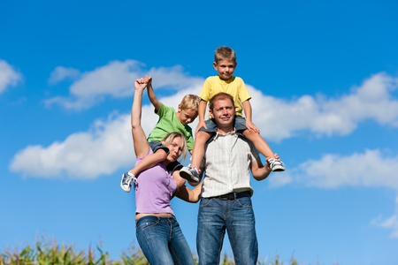 Family with two little boys on a summer meadow - the parents carry the sons on their shoulders   photo