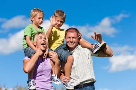 Familie mit zwei kleinen Jungen auf einer Sommerwiese - die Eltern tragen die Söhne auf ihren Schultern