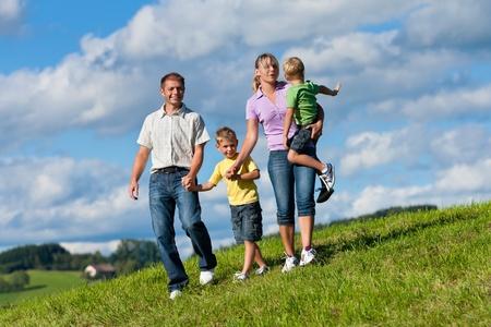 幸せな家族 (父、母と 2 人の息子) 美しい夏の日に散歩を持つ