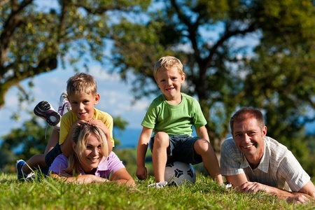 Family with two little boys playing in the grass on a summer meadow    photo