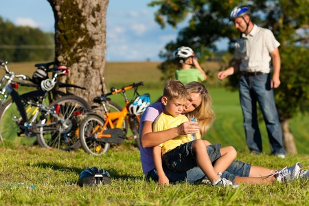 Happy family (father, mother and two sons) on getaway with bikes - they have a break Stock Photo - 11530328
