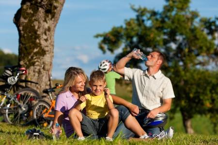 Gl�ckliche Familie (Vater, Mutter und zwei S�hne) am Wochenende mit Fahrr�dern - sie haben eine Pause