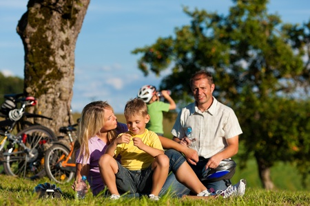 getaways: Happy family (father, mother and two sons) on getaway with bikes - they have a break