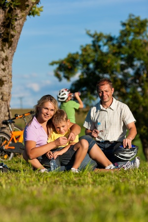 Happy family (father, mother and two sons) on getaway with bikes - they have a break photo