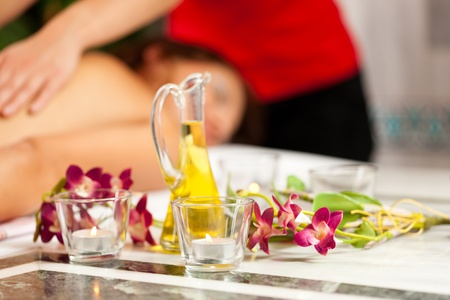 Wellness - woman getting massage in Spa; it is a traditional back massage, focus on massage oil in front Stock Photo - 11530212