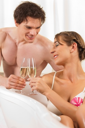 wife of bath: Couple is doing wellness with champagne; presumably it is their honeymoon Stock Photo