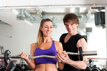 Young couple exercising in gym with weights; the man seems to be the personal trainer Stock Photo - 11530284