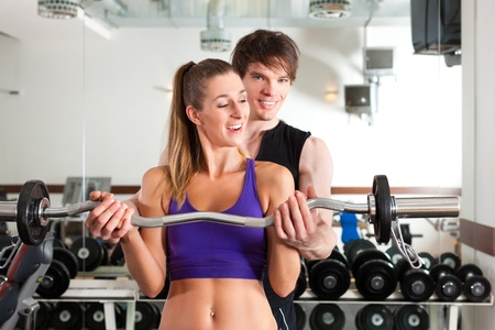 Young couple exercising in gym with weights; the man seems to be the personal trainer photo