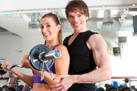 health club: Young couple exercising in gym with weights; the man seems to be the personal trainer