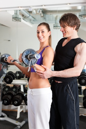 Young couple exercising in gym with weights; the man seems to be the personal trainer Stock Photo - 11530294
