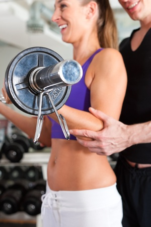 Young couple exercising in gym with weights; the man seems to be the personal trainer Stock Photo - 11530256