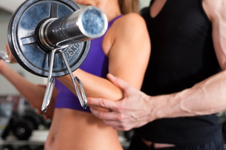personal trainer: Young couple exercising in gym with weights; the man seems to be the personal trainer