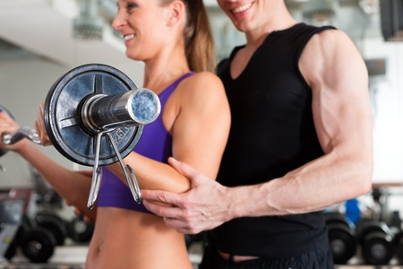 personal trainer woman: Young couple exercising in gym with weights; the man seems to be the personal trainer