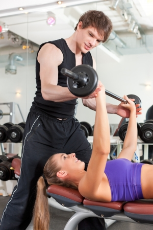 Young couple exercising in gym with weights; the man seems to be the personal trainer Stock Photo - 11530308