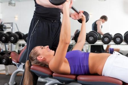 muskeltraining: Junges Paar in der Aus�bung Fitnessstudio mit Gewichten, der Mann scheint das Personal-Trainer sein