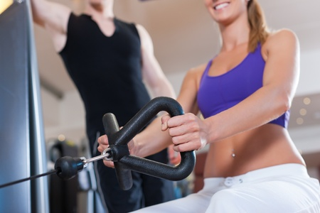 strengthen: Young couple exercising in gym on different power machines to strengthen the muscles; the man is personal trainer