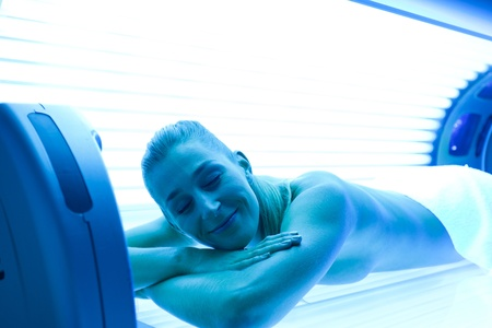 light complexion: Young woman lying on tanning bed for a beautiful complexion Stock Photo