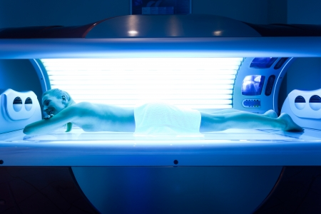 uv: Young woman lying on tanning bed for a beautiful complexion Stock Photo