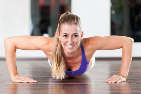 fitnesscenter: Muscular woman exercising by doing pushups in a gym