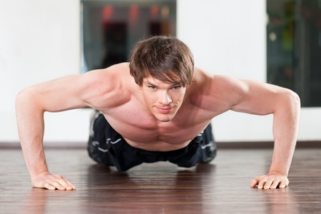 Muscular man exercising by doing pushups in a gym Stock Photo - 11530179