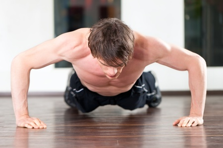 Muscular man exercising by doing pushups in a gym photo
