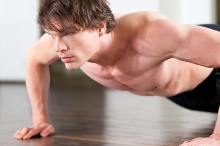 fitnesscenter: Muscular man exercising by doing pushups in a gym