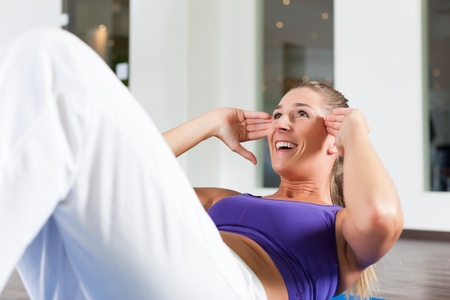 fitnesscenter: Young woman exercising by doing sit-up in a gym