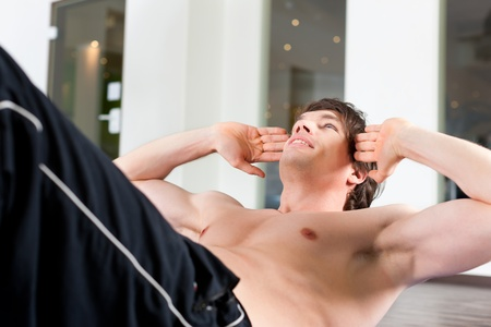 fitnesscenter: Young man exercising by doing sit-up, sit ups� in a gym Stock Photo