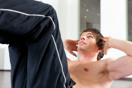 situp: Young man exercising by doing sit-up, in a gym