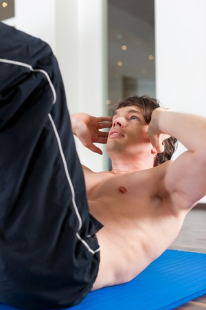 fitnesscenter: Young man exercising by doing sit-up, in a gym