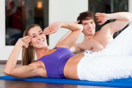 fitnesscenter: Young couple - man and woman - exercising by doing sit-up, in a gym