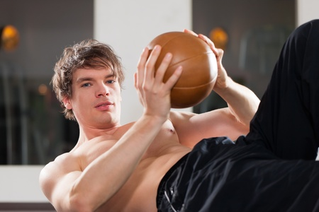 Young man is exercising with medicine ball in gym to strengthen his muscles photo