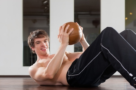 strengthen: Young man is exercising with medicine ball in gym to strengthen his muscles Stock Photo