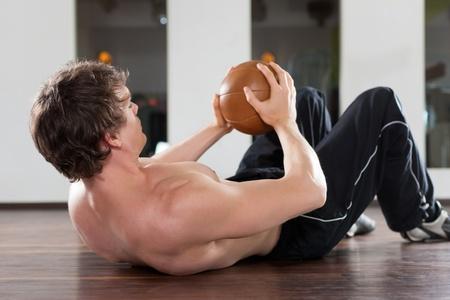 muskelaufbau: Junger Mann mit Medizinball Training in der Turnhalle, um seine Muskeln zu st�rken