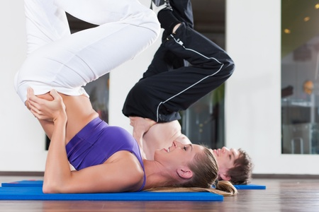 fitnesscenter: Sport and fitness - young couple is doing gymnastics in gym