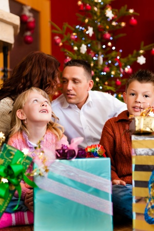 christmas eve: Christmas - happy family (parents with son and daughter) with gifts on Xmas Eve