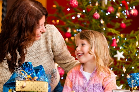 unwrapping: Christmas - happy family (mother with daughter) with gifts on Xmas Eve Stock Photo