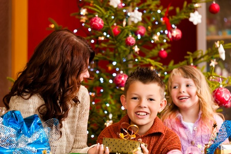 opening party: Christmas - happy family (mother with son and daughter) with gifts on Xmas Eve Stock Photo