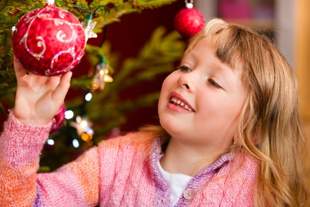 decorating christmas tree: Young girl helping decorating the Christmas tree, holding some Christmas baubles in her hand