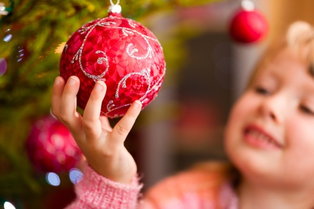 Young girl helping decorating the Christmas tree, holding some Christmas baubles in her hand  photo