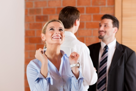 accommodation broker: Couple renting apartment from a realtor - a woman is happy about it and stands in the front while in the back the men shaking hands