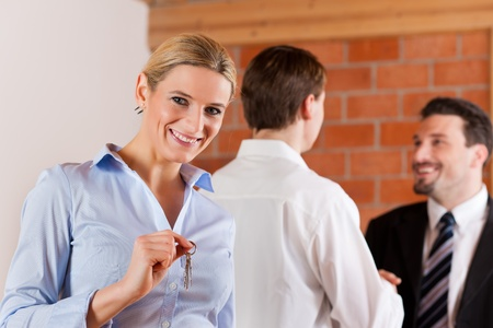 Couple renting apartment from a realtor - a woman is happy about it and stands in the front while in the back the men shaking hands photo