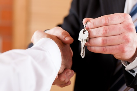 accommodation broker: Two businessperson shaking hands; only hands to be seen and a key is be given Stock Photo